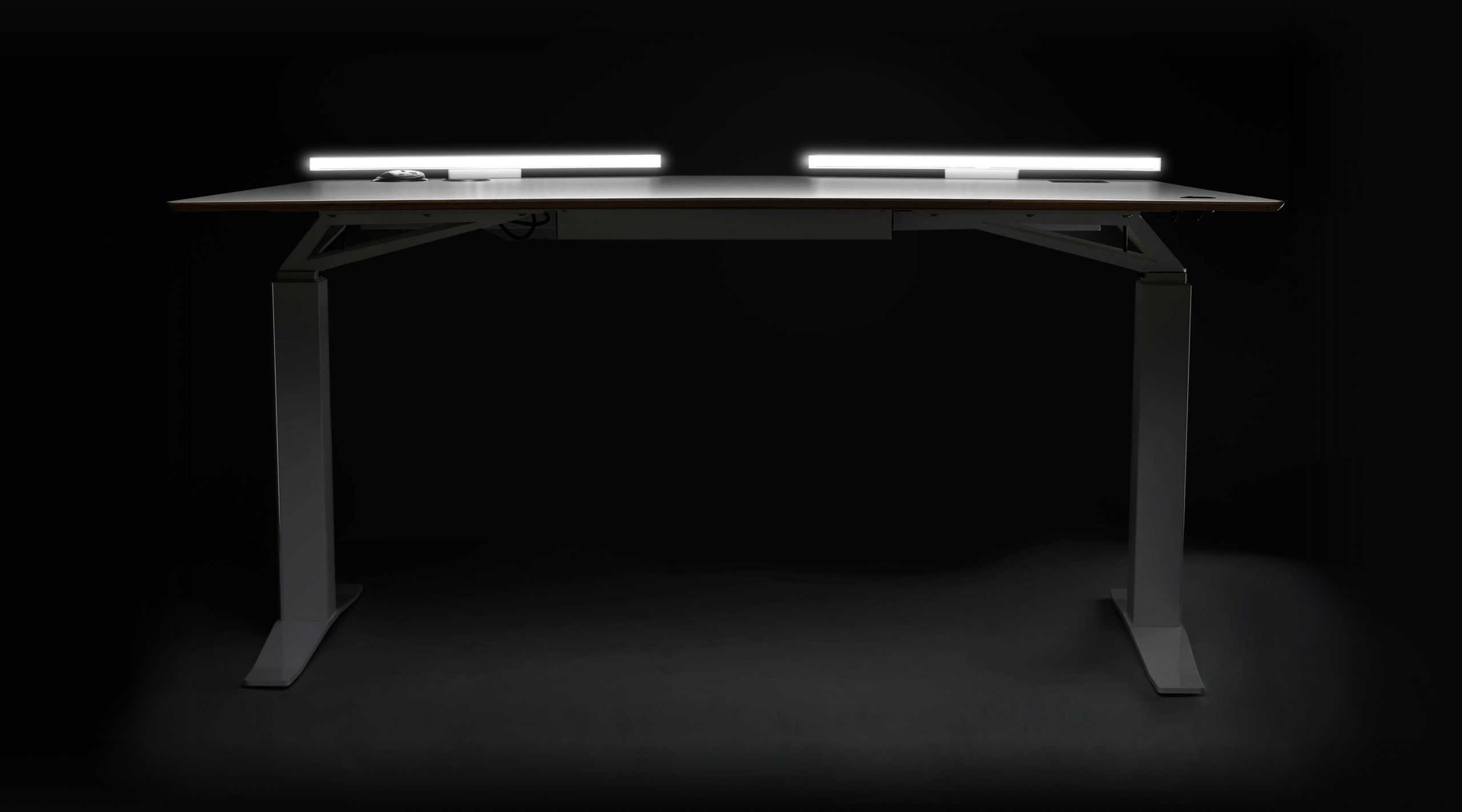 V-DESK Designer front - The ultimate electric height adjustable standing desk with Lightbar, power outlets and a dedicated space for your monitor mount. Sit stand desk made in the UK.